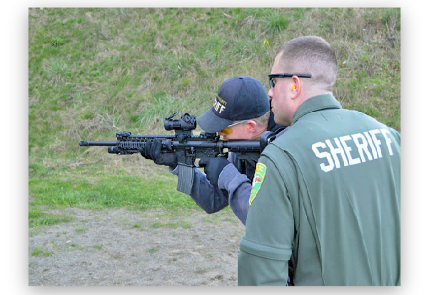 Deputy runs through the patrol rifle qualifications under the watchful eye of a firearms instructor